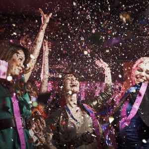 Laughing friends under falling confetti